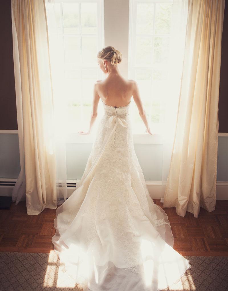 Bride in dress by window